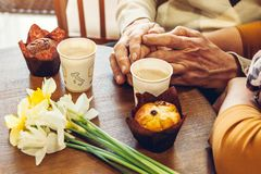 Senior couple holds hands in the cafe drinking coffee. Celebrating anniversary. Closeup royalty free stock photography