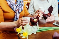 Senior couple holds hands in the cafe drinking coffee. Celebrating anniversary. Stock Image
