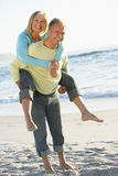 Senior Couple On Holiday With Husband Giving Wife Piggyback Royalty Free Stock Images