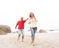 Senior Couple On Holiday Running Along Beach. Senior Couple On Holiday Running Along Winter Beach Royalty Free Stock Images