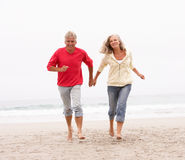 Senior Couple On Holiday Running Along Beach. Senior Couple On Holiday Running Along Winter Beach Royalty Free Stock Image
