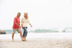 Senior Couple On Holiday Running Along Beach. Senior Couple On Holiday Running Along Winter Beach Stock Photography