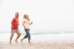 Senior Couple On Holiday Running Along Beach. Senior Couple On Holiday Running Along Winter Beach Royalty Free Stock Photography