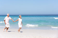 Senior Couple On Holiday Running Along Sandy Beach Stock Image