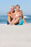 Senior Couple On Holiday Sitting On Sandy Beach Stock Photos