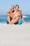 Senior Couple On Holiday Sitting On Sandy Beach. Smiling At Camera Stock Photos