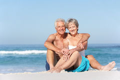 Senior Couple On Holiday Sitting On Sandy Beach Royalty Free Stock Photo