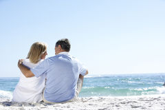 Senior Couple On Holiday Sitting On Sandy Beach Stock Photo