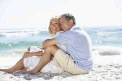 Senior Couple On Holiday Sitting On Sandy Beach Stock Images