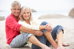 Senior Couple On Holiday Sitting On Winter Beach. Smiling At Camera Stock Photos
