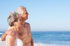 Senior Couple On Holiday Walking Along Sandy Beach. Smiling stock photography