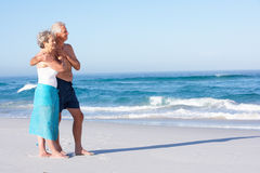 Senior Couple On Holiday Walking Along Sandy Beach. Smiling royalty free stock photo