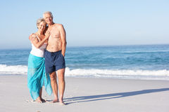 Senior Couple On Holiday Walking Along Sandy Beach Royalty Free Stock Photo