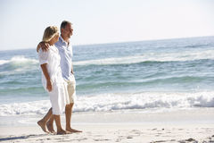 Senior Couple On Holiday Walking Along Sandy Beach Stock Photo