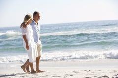 Senior Couple On Holiday Walking Along Sandy Beach Stock Photo