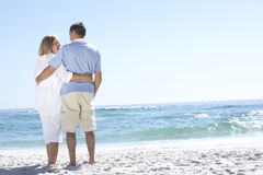 Senior Couple On Holiday Walking Along Sandy Beach Looking Out To Sea Royalty Free Stock Image