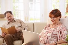 Senior couple at home. Senior couple resting at home reading book and browsing internet on laptop computer Stock Photos