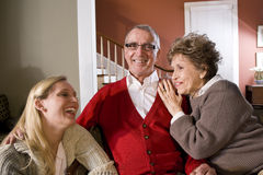 Senior couple at home with adult daughter Stock Images