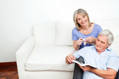 Senior couple at home on couch. Senior couple sitting at home on couch and reading and knitting Royalty Free Stock Photo