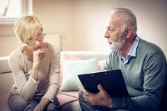 Contractor. Senior people. Senior couple at home with document and contractor stock photo