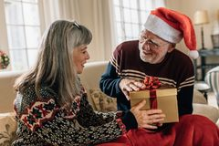 Senior couple at home exchanging christmas gifts royalty free stock images