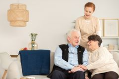 Senior couple at home. Happy senior couple sitting on a sofa and their nurse at home royalty free stock images