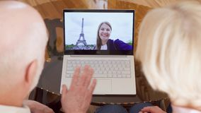 Senior couple at home having video chat with student daughter from Paris, Eiffel Tower on background. Top view of retired senior couple at home having video chat stock footage