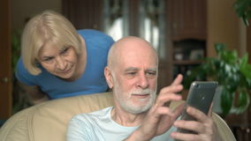 Senior couple at home. Husband using smartphone. Wife spying on her husband from his shoulder