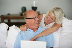 Senior couple at home with laptop computer Royalty Free Stock Photography