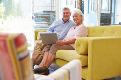 Senior Couple At Home In Lounge Using Laptop Computer Stock Images
