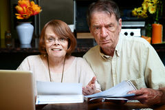 Senior couple at home with many bills Royalty Free Stock Image