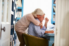 Senior Couple In Home Office Looking At Laptop Stock Photo