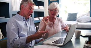 Senior Couple In Home Office Looking At Laptop And Arguing stock video