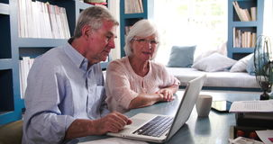 Senior Couple In Home Office Looking At Laptop. Senior couple using laptop sitting at desk in home office reviewing domestic finances.Shot in 4k on Sony FS700 at stock video