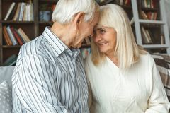 Senior couple at home retirement concept heads together close-up. Aged men and women at home in the living room sitting on the coach heads together looking on stock photo