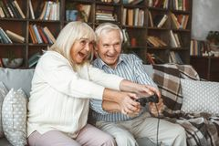 Senior couple at home retirement concept sitting holding controller together excited. Aged men and women holding game controller together at home in the living stock photos