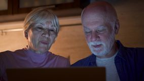 Senior couple at home use laptop in kitchen at night. Retired family of pensioners work on computer. Senior couple at home using laptop in kitchen at night stock footage