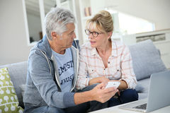 Senior couple at home using smartphone and laptop Royalty Free Stock Images