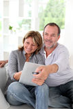 Senior couple at home watching tv and using tablet Stock Photos