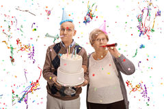 Senior couple with horns and party hats celebrating birthday Royalty Free Stock Image