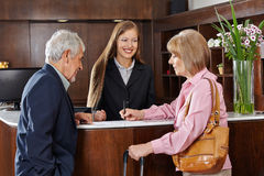 Senior couple in hotel signing form Royalty Free Stock Images