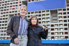 Senior couple with house key in hand against blue blank banner on building Stock Photo