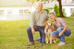 Senior couple with house and labrador retriever Stock Images