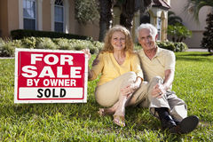 Senior Couple and House For Sale Sold Sign Royalty Free Stock Photography