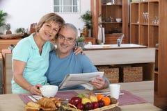 Senior couple hugging. Happy senior couple ehugging in the kitchen Stock Images