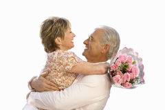 Senior couple hugging, bunch of roses, cut out royalty free stock image