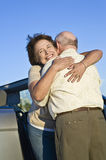 Senior Couple Hugging In Front Of Car. Happy senior couple standing in front of car and embracing Royalty Free Stock Images