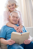 Senior couple hugging and relaxing, man reading book. Happy senior couple hugging and relaxing, men reading book Royalty Free Stock Photos