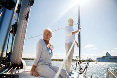 Senior couple hugging on sail boat or yacht in sea. Sailing, age, tourism, travel and people concept - happy senior couple hugging on sail boat or yacht deck stock images