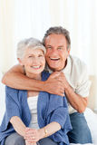 Senior couple hugging on their bed Stock Photo